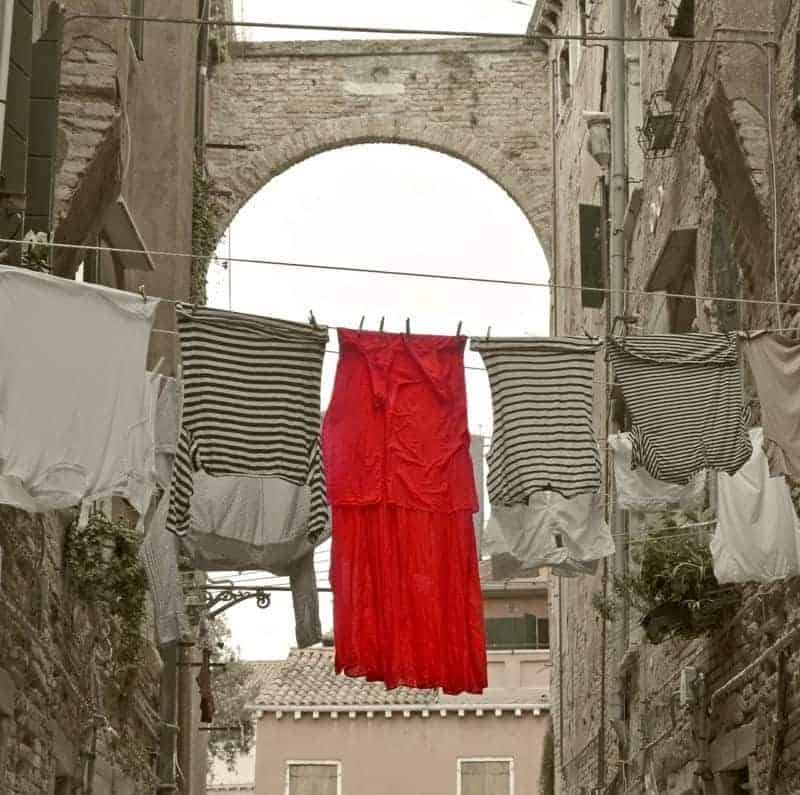red dress and shirts on clothes line in Venice italy