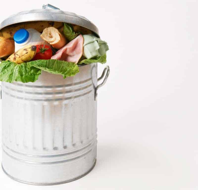 food scraps in metal trash can.