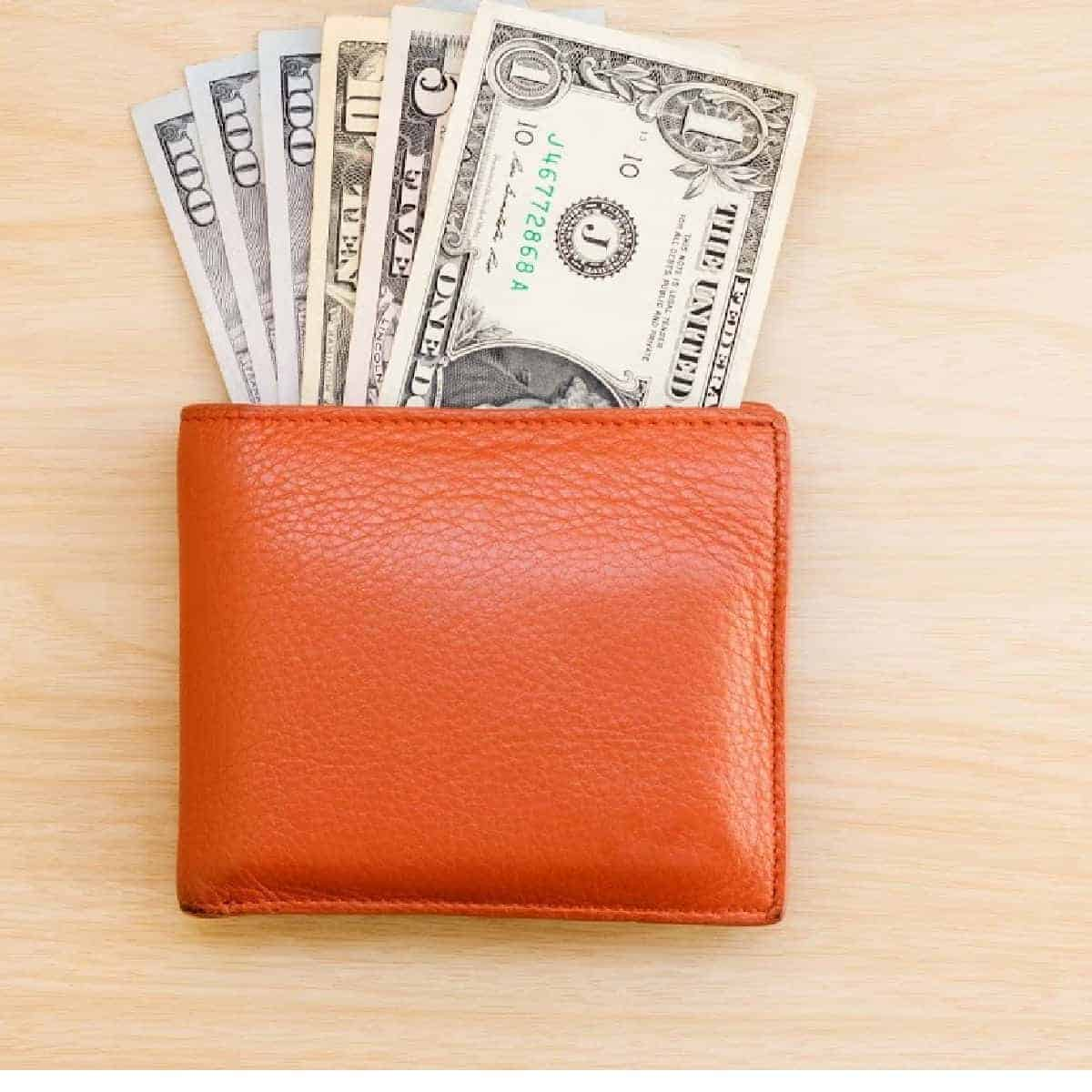 orange wallet with money coming out.
